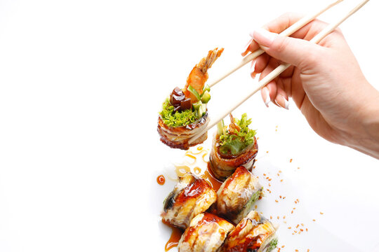 Eating a sushi set with chopsticks, on a white background. Female hand with wooden chopsticks holding unagi ebi roll with an eel, a shrimp in tempura and a cucumber.