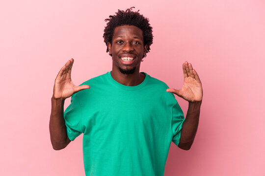 Young african american man isolated on pink background holding something with palms, offering to camera.