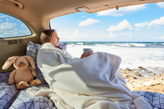 A young woman is dreaming in a car by the ocean.