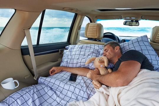 A young man sleeps in a hugging with a stuffed rabbit in the car by the ocean.