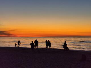 Fototapeta Ludzie i zachód słońca nad morzem bałtyckim obraz