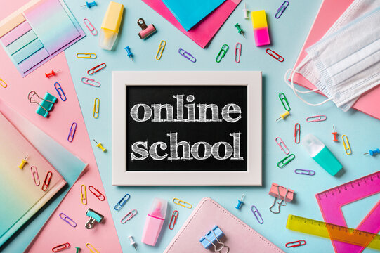 Black chalkboard with letters online school. School supplies, pencils, scissors and colored books on blue and pink background. Top view or flat lay. E-learning concept