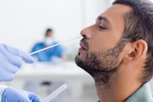 doctor in latex gloves taking samples for coronavirus test from man in hospital