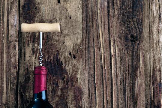 Wine bottle and wine opener on wood