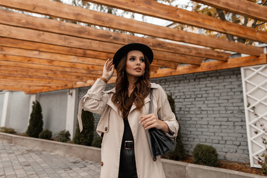 Fashionable elegant beautiful girl with a stylish hat in a trendy beige coat with a black leather bag walks on the street. Female style and beauty