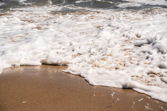 Ocean Nature image of close-up details as foamy water as waves wash up on shore at the beach