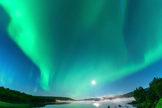 Panoramic Aurora borealis, Northern green lights with full moon and stars in the night sky over mountain lake, mirrored reflection in water, night mist. Night road, Joesjo, Lappland, Northern Sweden