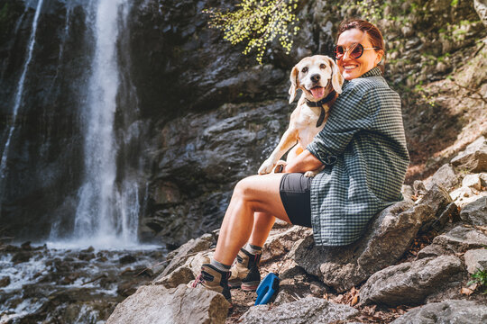 Smiling Female dog owner hugging his friend beagle dog resting near the mountain river waterfall during their together walking in autumn season time. Human and pets or walking in nature concept image.