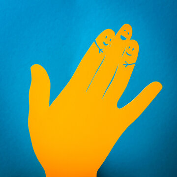 Papercut concept of three fingers hugging themselves. Happy orange paper hand on the blue background.