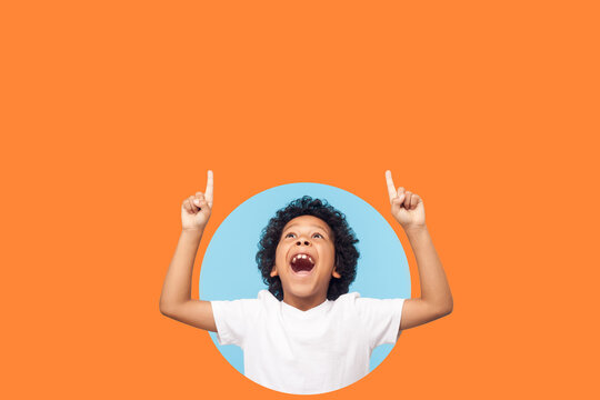 Wow, look up! Amazed boy pointing up to empty place on background, shocked, surprise with open mouth and showing copy space for advertisement. indoor, isolated in a round hole on orange background