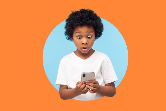 shocked boy with curly hair reading message on smartphone and shocked, surprised by mobile application, using cellphone. indoor studio shot isolated in a round hole on orange background