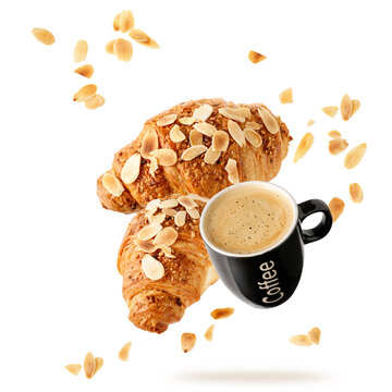 Fresh baked almond  breakfast croissants  with nuts crumbs and black cup hot espresso coffee flying isolated on white