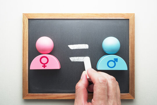 Gender equality. Female and male symbols. Hand writing equal sign on blackboard.