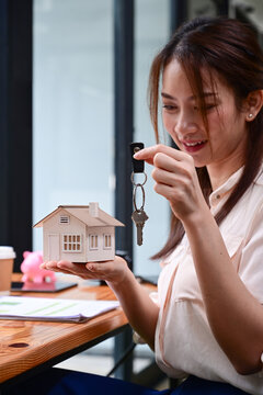 Smiling female real estate agent holding house keys and house model. Property investment concept.