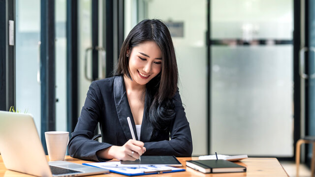 Beautiful Asian businesswoman work using a tablet and a laptop with documents placed at the office.