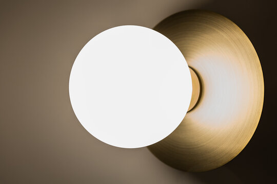 Brass wall light with frosted globe