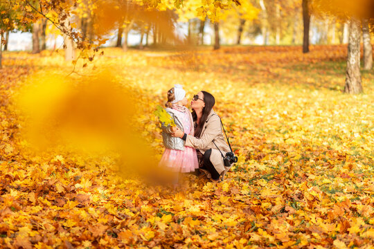 Mom with a baby daughter in stylish clothes with a camera kiss on the background of bright fall yellow foliage in the park. Family walk and photo session on golden autumn nature