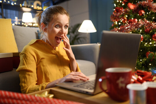 Cheerful surprised woman social networking at Christmas