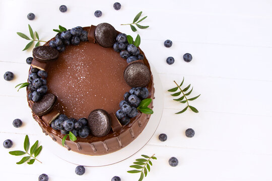 Delicious chocolate  cake with fresh   blueberry ,  top view , white  wooden board