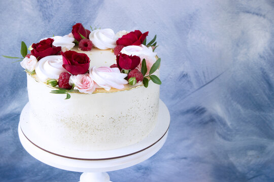 Modern  cake   with fresh red roses on white wooden cake stand, copy space . Concept for Wedding , St. Valentine's Day, Mother's Day, Birthday Cake.