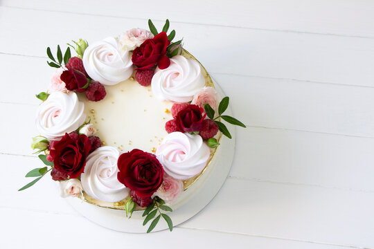 Modern  cake   with fresh red roses  and raspberries on white wooden board, copy space . Concept for Wedding , St. Valentine's Day, Mother's Day, Birthday Cake.