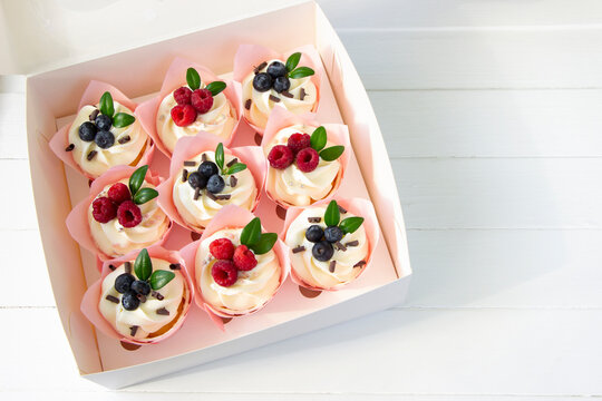 Cupcakes  decorated with raspberry and blueberries  in delivery paper box. Sweet food delivery