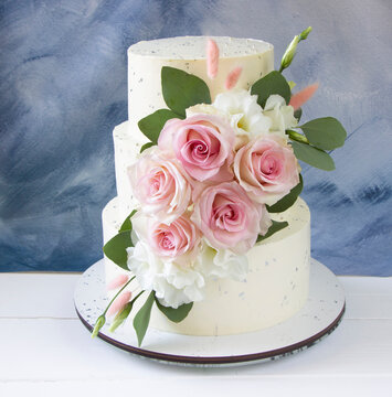 Modern wedding cake with pink and white fresh roses . Blue background