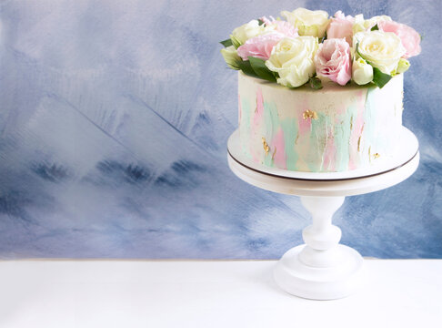 Modern wedding cake with pink and white fresh roses on cake stand. Blue background. Cake design template with space for text