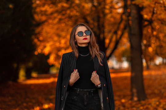 Portrait of a beautiful fashionable girl with sunglasses in a fashion black suit with a blazer and a sweater walks in the park with colorful golden foliage