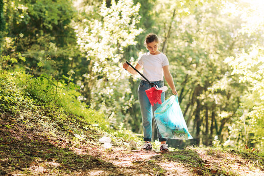 Girl cleaning up the forest and collecting trash