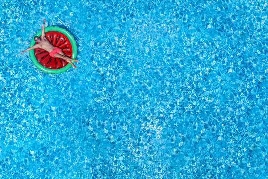 A man enjoys on a watermelon shaped float the summer sun in a big swimming pool