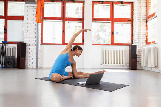 Flexible young woman doing stretching in front of a laptop