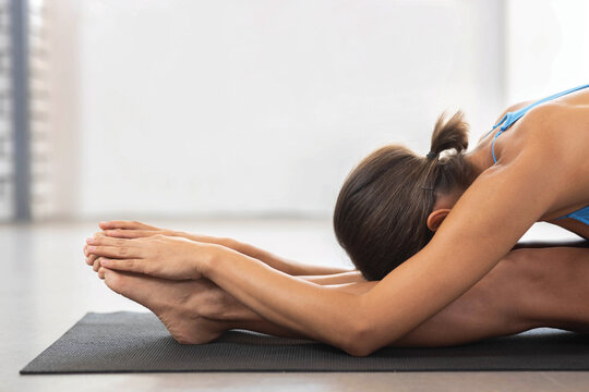 Brunette woman doing stretching workout exercises while sitting on the floor, yoga
