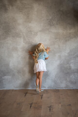 Obraz Portrait of a girl, there are many interesting emotions on her face. Great for demonstrating the character of a child - thoughtfulness, daydreaming, aspiration, growth, thoughts, smile. Background gra - fototapety do salonu