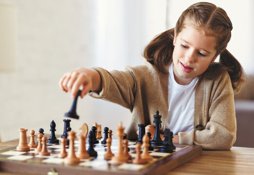 Cute little girl playing chess while spending leisure time at home during during day time, child sitting at table in living room and moving figure on chessboard with concentrated face expression