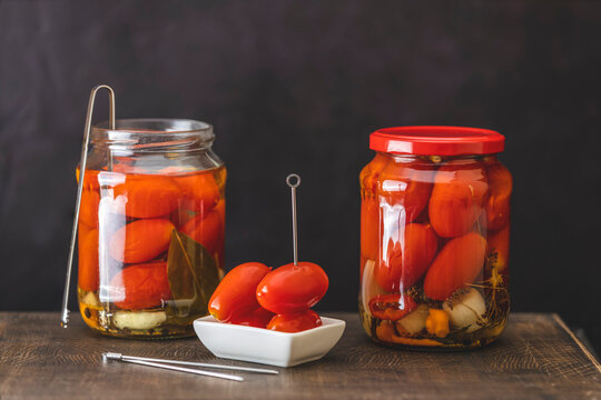 Pickled red cherry tomatoes in a glass jar on the old wooden background, selective focus