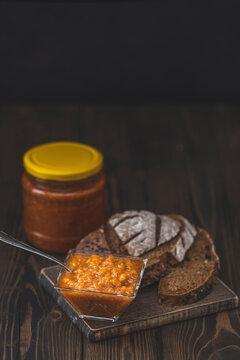 Squash zucchini paste or caviar and rye bread on dark wooden table
