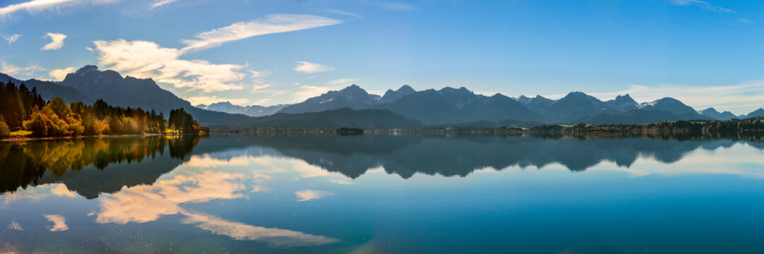 panoramic landscape in Bavaria at lake Forggensee mirroring alps mountains