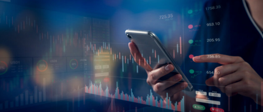 Stock exchange market concept, hand using smartphone with graphs analysis candle line on bokeh colors light.