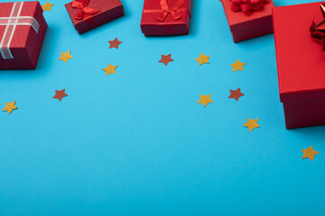 Composition of presents with stars and copy space on blue background