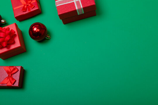 Composition of baubles with presents and copy space on green background