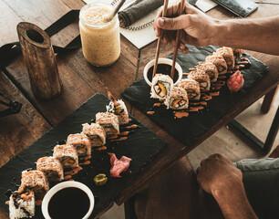 Fototapeta Sushi podane na kamieniu podane w restauracji na tle ciemnego drewnianego stołu. obraz