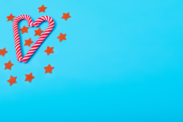 Composition of candy canes with stars and copy space on blue background