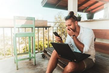 Mężczyzna, cyfrowy nomada pracujący z laptopem i rozmawiający przez telefon komórkowy w słoneczny dzień.