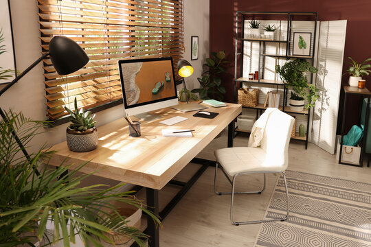 Light room interior with comfortable workplace near window