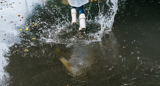 Crop girl in gumboots running on puddle with splashing water