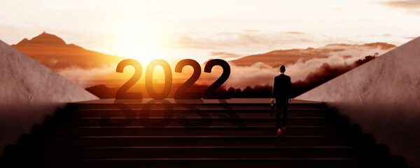 Fototapeta new year 2022 with business people walking to success silhouette obraz