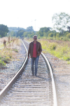 lonely man walking on railroad tracks