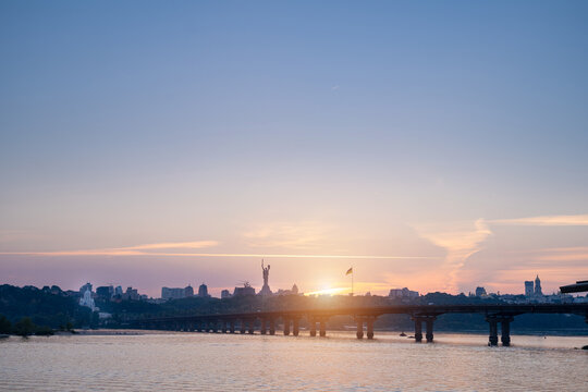 Beautiful view to the right side of Kyiv (Kiev) Ukraine. River Dnieper, Paton Bridge, Kyiv Pechersk Lavra and Motherland Monument main popular sightseeing places. Summer Sunset romantic soft light