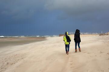 Fototapeta Sztorm na morzu bałtyckim, a na plaży piaskowe szaleństwo. Strumień piasku smaga po twarzy, silny wiatr unosi smugi pyłu i utrudnia spacer. Matka z synem z trudem idą pod wiatr. obraz